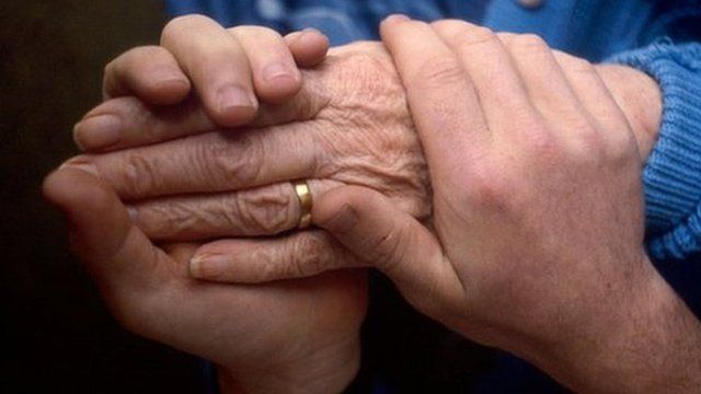 Health carer holding the hand of an elderly patient.
