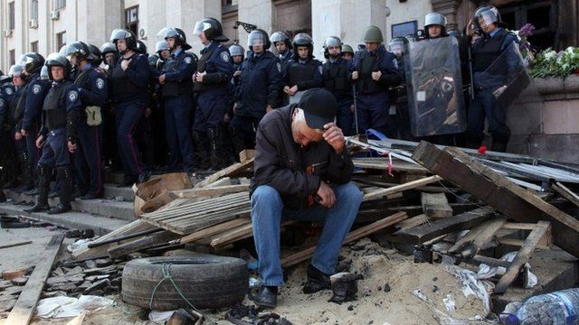 A Pro-Russian activist sits in front of policemen guarding the burned trade union building in the southern Ukrainian city of Odessa