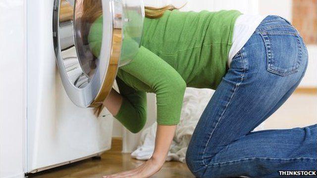 woman looks in washing machine