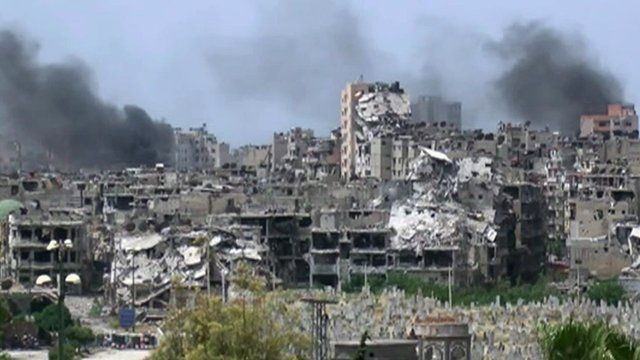 Smoke above destroyed buildings in Homs