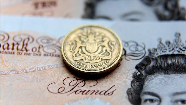 Sterling pound coin in front of a ten pound note
