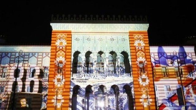 3D mapping projections of the logo of the 1982 Sarajevo Winter Olympics are seen on the facade of the City Hall