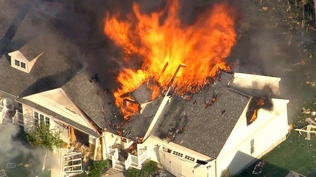 In this frame grab from television helicopter video, a home bursts into flames in Brentwood, N.H