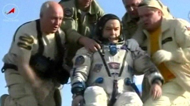Mikhail Tyurin is helped out of the space capsule