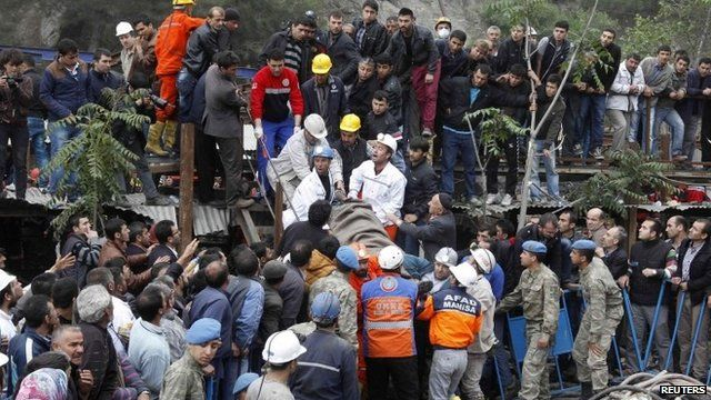 Crowds watch as rescuers carry injured miner from scene