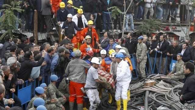 Rescuers carry a miner who sustained injuries after a mine explosion