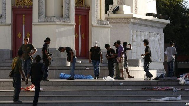 Volunteers from anti-government protesters clean up after an overnight shooting attack at Democracy Monument in Bangkok on 15 May.