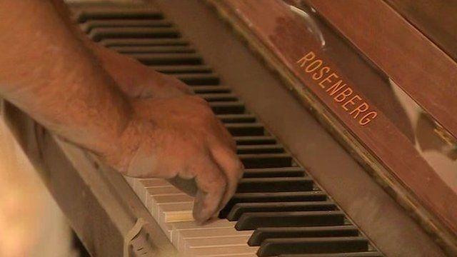 Man plays dusty piano inside Homs
