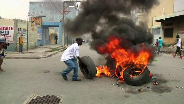 A protester burns a tyre on the streets of Port-au-Prince