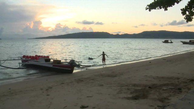 Boy and boat at a beach