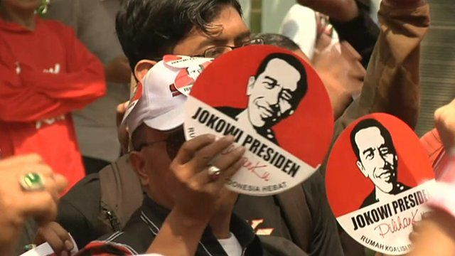 Crowd holding up Jokowi election signs