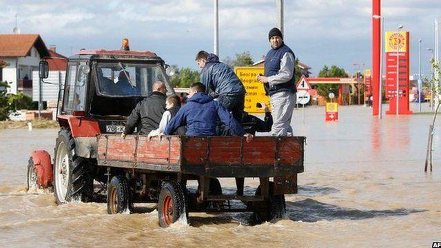 Bosnian men ride a tractor in a flooded street in the eastern-Bosnian town of Bijeljina