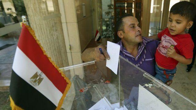 Egyptian man holding his son