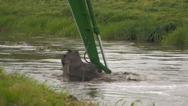 A bucket dredging silt from a river in Somerset