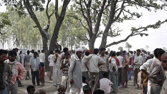 Onlookers stand at the site where two teenage girls, who were raped, were hanged from a tree