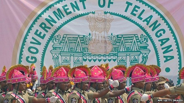 Newly-formed Telangana state policemen march past the new state's coat-of-arms