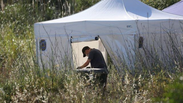 A British police officer sifts through soil under a white tent, after it was removed from a site of an area of wasteland during a search for evidence of Madeleine McCann in the town of Praia da Luz, Portugal