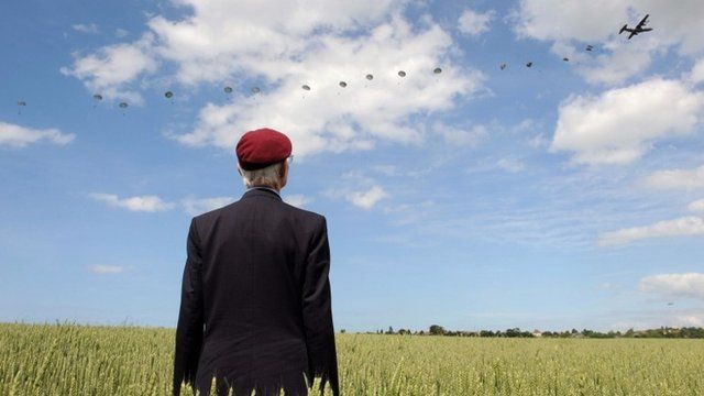 British World War Two veteran Frederick Glover poses for a photograph as soldiers parachute down during a D-Day commemoration paratroopers launch event in Ranville, northern France, on June 5, 2014