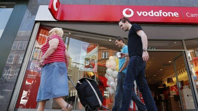 People walk past a Vodafone shop in London, on Friday, June 6, 2014