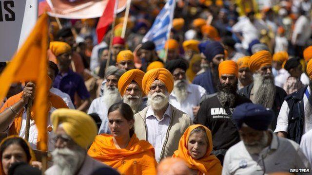 Sikhs, wearing orange, marching
