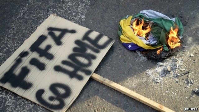 'Fifa go home' sign next to burning Brazilian flag