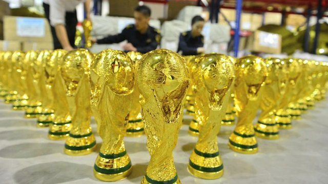 Warehouse floor covered in fake World Cup trophies