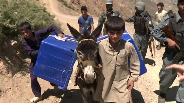 Boy leading donkey carrying ballot boxes