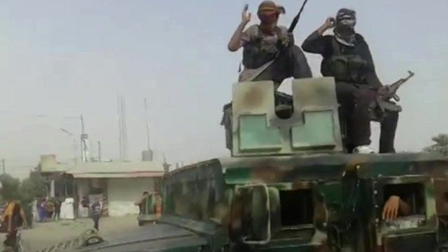 armed militants on top of vehicle
