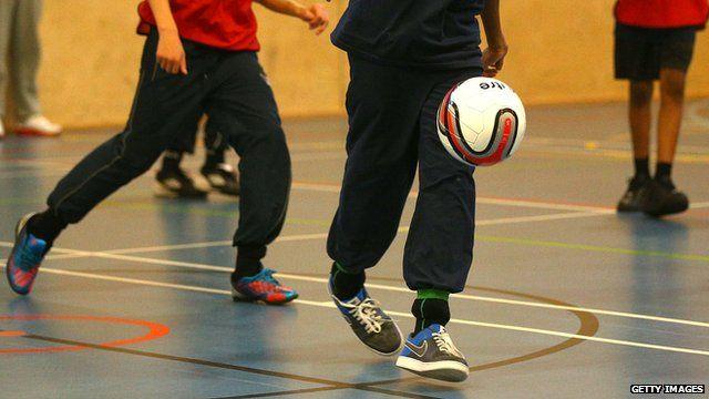Children playing football in a school gym
