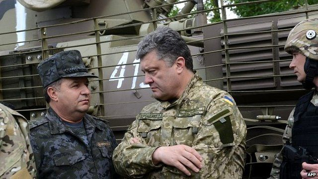 Ukrainian President Petro Poroshenko, wearing military fatigues, speaks with Ukrainian army's Anti-Terrorist Operation (ATO) officers at their headquarters