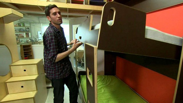 Juan Hernandez lowers a fold-away bunk bed