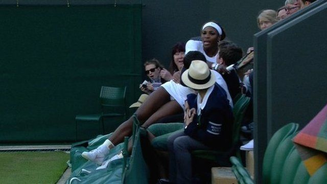Serena Williams falls into a spectator's lap at Wimbledon during a doubles' match on day three