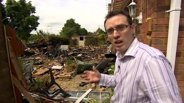 BBC reporter Neil Bradford pointing out debris from gas explosion