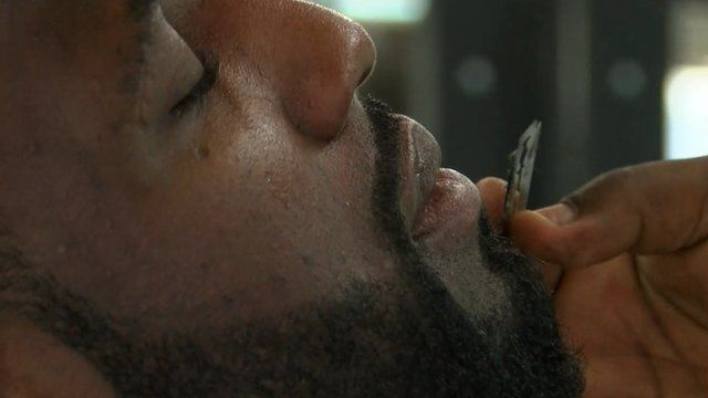 A footballer having his beard groomed at the barbers