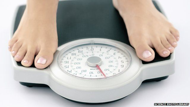 Woman stands on bathroom scales - posed by a model