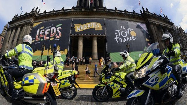 British policemen, working on Tour de France security, ride past the city hall of Leeds, northern England, on July 4, 2014