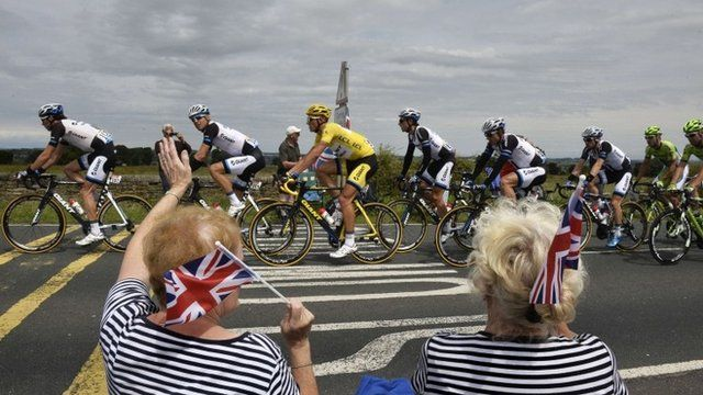 Supporters wave along the road as Germany's Marcel Kittel (C), wearing the overall leader's yellow jersey