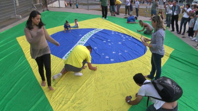 Brazilian fans sign the national flag