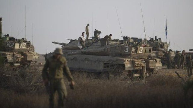 Israeli soldiers work on their tanks at a staging area near the Israel-Gaza Border, 9 July