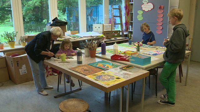 Older woman teaching children art