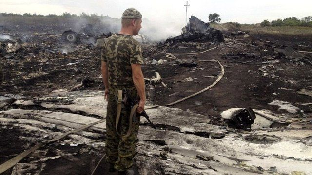 armed man at a site of a Malaysia Airlines Boeing 777 plane crash