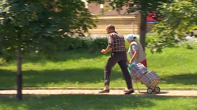 Elderly couple run along path with bags on trolley