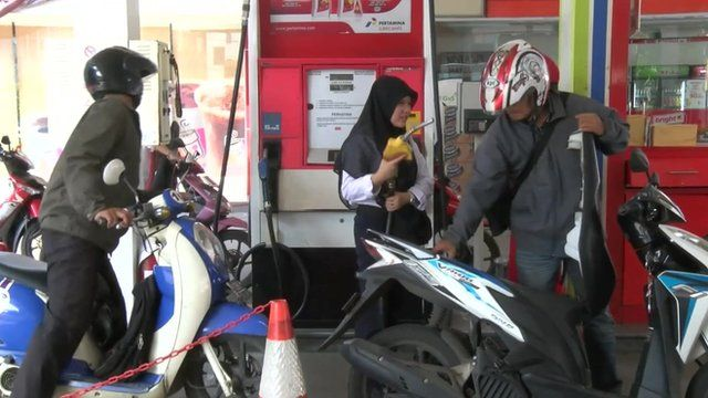 Motorcyclists at a petrol station in Indonesia
