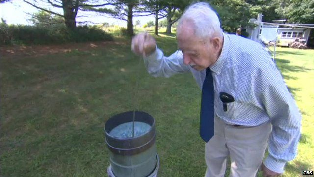 101-year-old volunteer weather observer, Richard G Hendrickson, measuring rainfall
