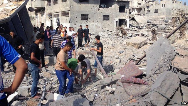 Residents in Shujaiya pick through the rubble (26 July 2014)