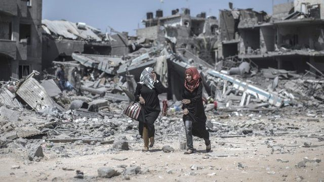 Two Palestinian women react to the scene of devastation behind them as they walk past destroyed houses in Beit Hanoun northern Gaza Strip, 26 July