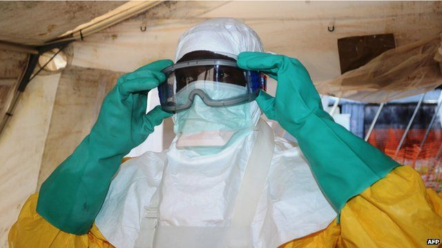 A medical worker puts on a mask