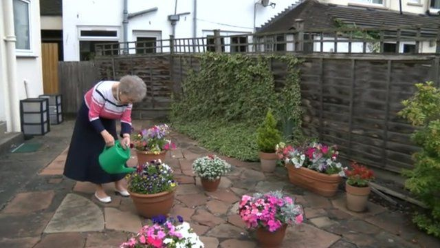 Jean Hall watering plants in her garden