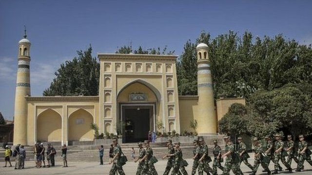 Chinese soldiers march in front of the Id Kah Mosque,