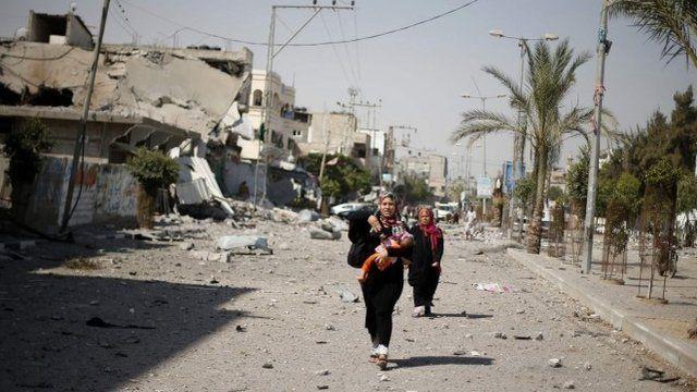A Palestinian woman walking along a street in Beit Hanoun town